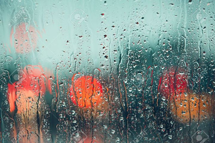 58733306-heavy-rain-raindrop-on-the-window-of-the-car-abstract-blur-bokeh-of-traffic-and-car-light-